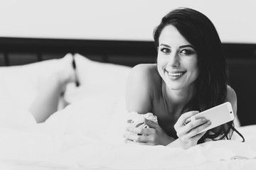 portrait of the beautiful young woman lying on the bed with mobile phone