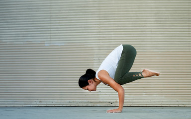 Outdoor Fitness Female Yoga Instructor in Crow Pose