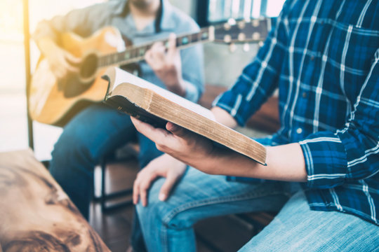 close up of a man holding hymn books and sing a song while his friend playing guitar, praise and worship concept