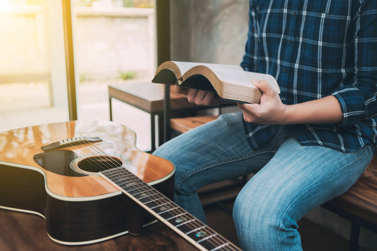 close up of a man hands holding  and read book  with guitar on wooden table, christian background, devotional concept