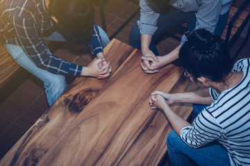Christian people prays together around wooden table. prayer meeting small group concept.