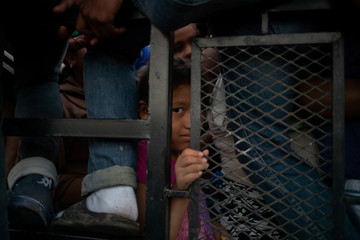 Girl traveling with migrant caravan from Central America en route to U.S. looks out from open bed truck in Huixtla, Mexico