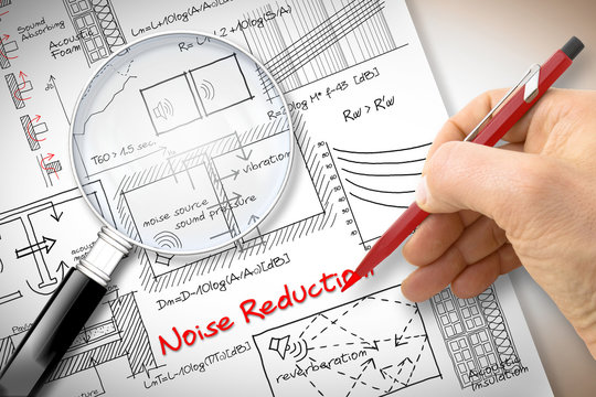 Engineer writing formulas about noise reduction in buildings - Concept image seen through a magnifying glass