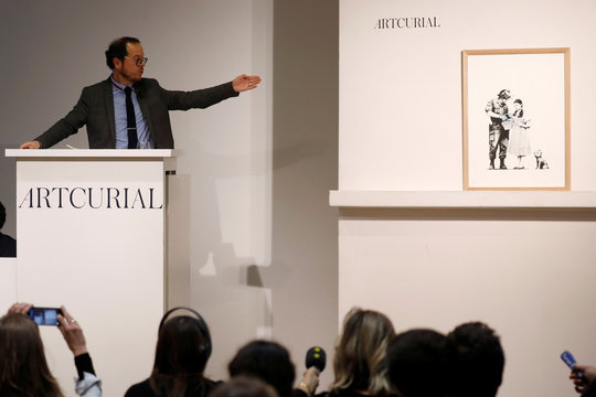 """Auctioneer Arnaud Oliveux points at the offset lithograph entitled """"Stop and Search"""" (2007) by British street artist Banksy at the urban art auction organized by Artcurial in Paris"""