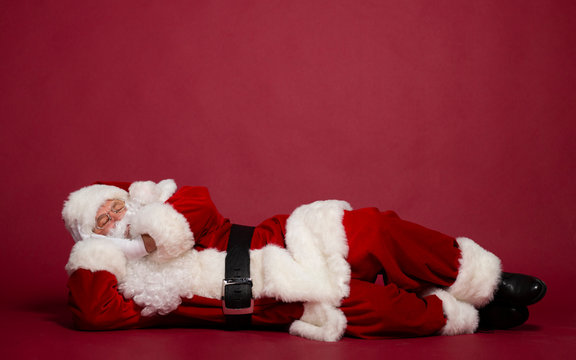 Santa Clause sleeping while lying on red background, Christmas and New year concept