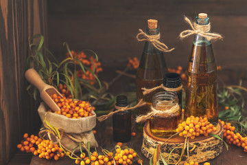 Natural, organic sea-buckthorn berry in linen bag and sea buckthorn oil in glass vintage bottles