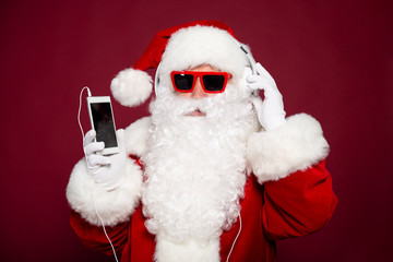 Funny and stylish Santa Clause holding smartphone and listening to music at headphone on red background, Christmas and New year concept
