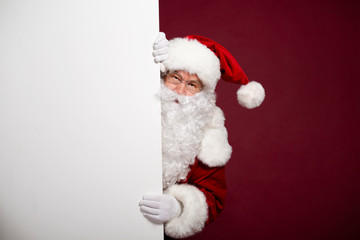 Man in Santa Clause costume looking out from behind white blank banner on red background, Christmas and New year concept