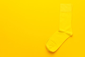 pair of socks on bright yellow background. top view of yellow socks with copy space