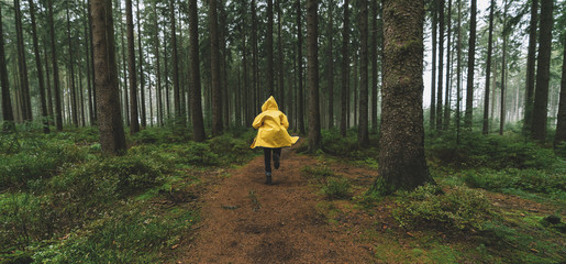 man in yellow rain jacket runs in the forest, fog, rain and mist