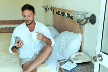 handsome man in white shirt enjoying working at home or hotel room, businessman calling room service and drinking cup of coffee making money. Man is busy working on a laptop calling his wife or a boss