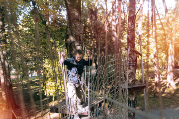 man, climbing gear in an adventure park are engaged in rock climbing or pass obstacles on the rope road, arboretum, insurance, attraction, amusement park, active recreation, autmn