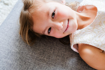Little Girl in Holiday Dress Sitting on Sofa