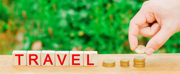 "wooden blocks and the inscription ""travel"" and a stack of coins. concept of saving and collecting money on travel. Budget for vacation and resort. accumulation savings plan"