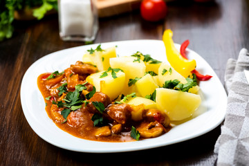 pork goulash served with boiled potatoes