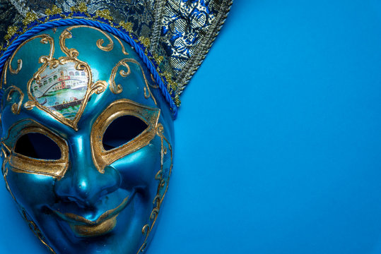 A blue Mardi Gras or carnival jester mask on a blue background