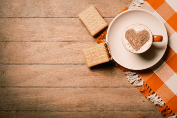 photo of the cup of coffee and cookies on the tablecloth on the brown wooden background