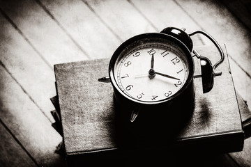 photo of the alarm clock and books on the brown wooden background . Image in black and white color style