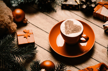 photo of the cup of coffee and christmas decorations on the brown wooden background