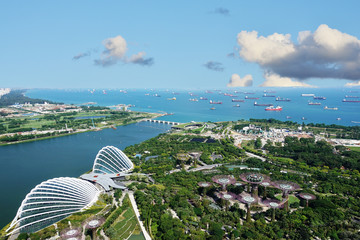 Foto op Canvas Singapore Singapore harbor with many transportation boats and Gardens by the Bay, aerial view from Marina Bay Sand hotel in a sunny day, Singapore, October 15, 2018