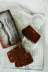 Chocolate cake with nuts inside cut into slices on cooling rack. A mini sieve with powdered sugar. Directly above, white background.