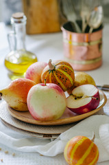 Still life with small pumpkins, apples and pears on a ceramic plate. Autumn still life in bright colors. Vegetables and fruits on the table with a white tablecloth.