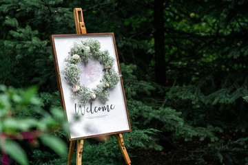 Blank signpost pointer on a wooden easel in a frame with a wreath. Welcome inscription Forest Wedding.