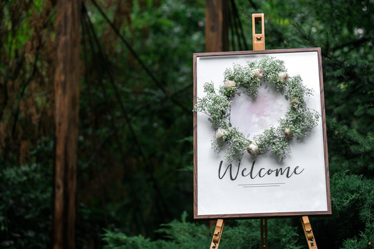The easel is wooden with a frame plate and the words welcome. Index of events in the forest, wedding decor.