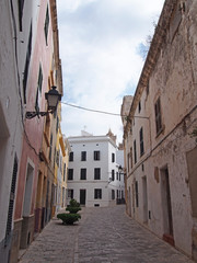 picturesque quiet empty typical street in ciutadella menorca with old traditional houses and a street lamp with blue cloudy sky