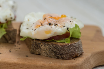 Poached eggs on a piece of rye bread with tomato and salad on a wooden cutting board