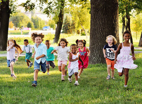 A group of happy children of boys and girls run in the Park on the grass on a Sunny summer day . The concept of ethnic friendship, peace, kindness, childhood.