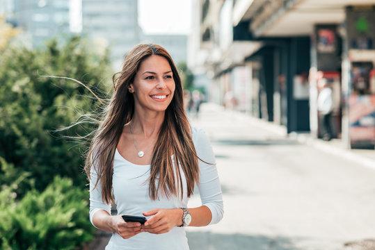 Beautiful girl walking in the city street.