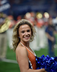 Young college cheerleader performing at a college football game