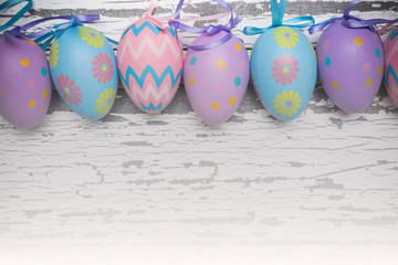 A group of pastel colored Easter eggs on a white, aged wooden background with copy space.