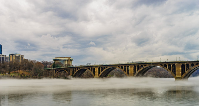Francis Scott Key Bridge across Potomac River, winter fog on the water.
