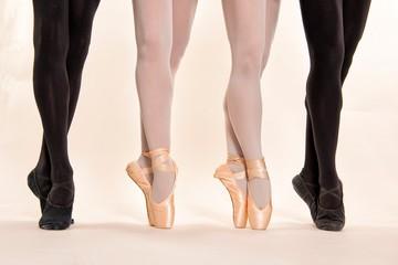 Zwei Tänzer außen in schwarz gekleidet und zwei Tänzerinnen innen stehen alle mit ihren Spitzenschuhen auf den spitzen