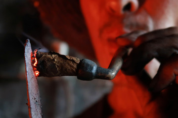 Blacksmith lights his pipe with a heated iron stick at a workshop for handmade woks in Datian village