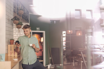 Young business owner drinking coffee, checking smartphone