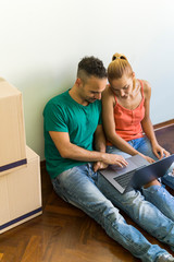 Couple sitting side by side on the floor of new home looking together at laptop