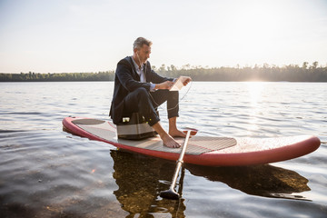 Businessman sitting on paddleboard on a lake using tablet and earphones