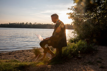 Mature businessman sitting at lakeshore by sunset working on laptop
