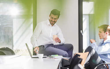 Two smiling colleagues working on project in office together