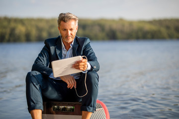 Portrait of relaxed businessman with earphones and tablet sitting on paddleboard at lake