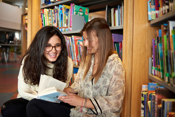 Two young women having fun in the library