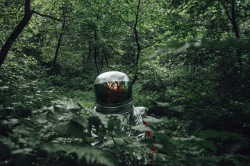 Spaceman exploring nature, looking at forest