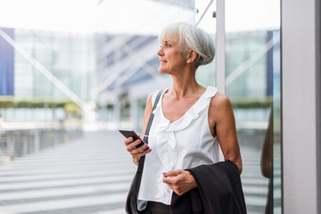 Senior woman with cell phone in the city looking around