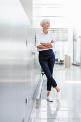 Smiling senior businesswoman leaning against a wall