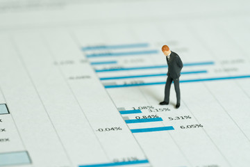 Investment, financial performance report analysis concept, miniature people figurine success businessman standing and jooking at stock exchange data graph and chart document