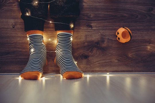 kids legs in stylish colorful striped socks in garland lights on floor with pumpkins in room. decor for Halloween, cosy moment. cozy autumn days. Happy Halloween celebration concept. vintage tone