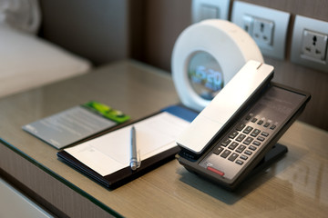 Black telephone and note in front and bed in the background, focus on the telephone,for room service,communication themes in hotel or resort..
